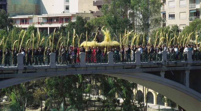 Bridge with a religious float and procession of people carrying palm leaves. Palm Sunday procession. Elche ©Turespaña