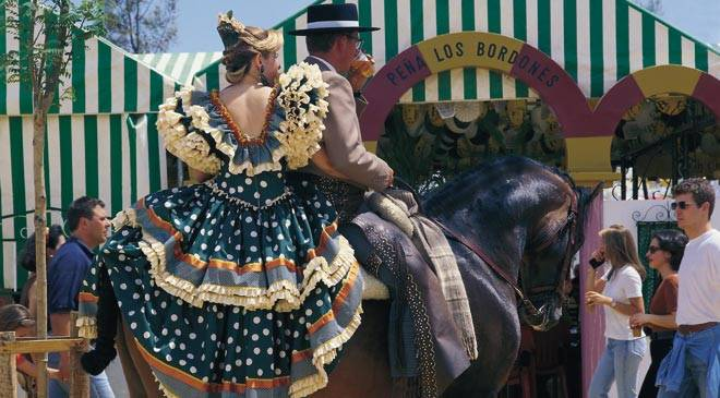 Couple in traditional dress on horseback. Cordoba Fair © Turespaña