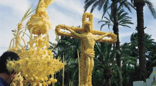 """Christ made of palm carried by various 'costaleros'. Palm Sunday procession. Elche ©Turespaña"""