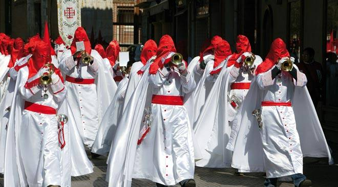 Religious brotherhood of El Santo Sepulcro playing their instruments in the Easter week procession in Medina del Campo.