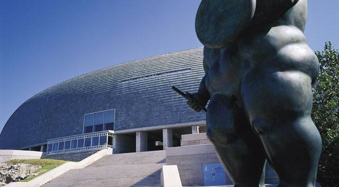 Domus. House of Man. View of the exterior of the museum with the sculpture by Botero, 'Roman soldier', in the foreground. A Coruña © Turespaña