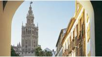 La Giralda tower with a crucifix in the foreground. Seville © Turespaña