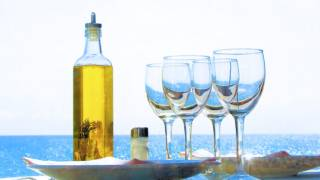 Table beside the Mediterranean, with olive oil and glasses.