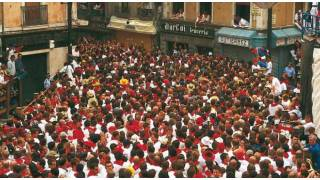The square packed with people waving red handkerchiefs during the festivities in honour of San Fermín. Pamplona-Iruña © Turespaña