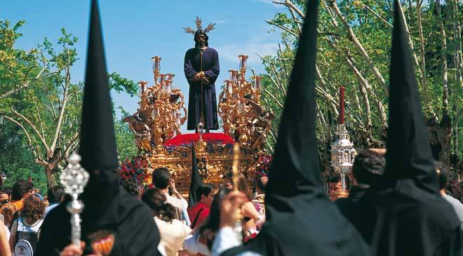 Front view of the religious float of the Captive Christ, surrounded by the public and penitents. Santa Genoveva religious association, Seville © Turespaña
